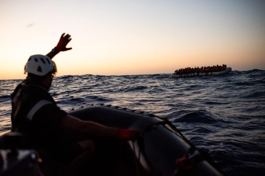 As weather conditions in the Mediterranean Sea rapidly deteriorated about 50 nautical miles from the Libyan shoreline, the Sea-Watch 4 this morning concluded its third rescue in less than 48 hours. Almost 100 people were drifting in a flimsy rubber boat between the Sabratah and Farwah oil fields.   In the night, the passengers of the boat had called and informed AlarmPhone about their distress and position. After AlarmPhone had informed the responsible authorities, the standby oil field vessel VOS Triton spotted the boat in the early morning hours. The fast rescue boat Louise Michel arrived on scene soon after and stabilised the situation, providing the passengers with life vests and closely observing the boat's condition, until the arrival of the Sea-Watch 4.  With the first light of the day the Sea-Watch and MSF crew then started the evacuation of the rubber boat, which was complicated by a heavy 2 meter swell. Nonetheless, all people were safely transferred to the Sea-Watch 4.   The majority of the rescued people were weak and disoriented, smelling strongly of gasoline and exhibiting symptoms of fuel inhalation. Upon preliminary assessment by MSF medics, emergency showers were provided for almost everyone, and the team will continue to monitor for fuel burns and effects of intoxication from exposure to gasoline fumes. The majority of those rescued this morning are in poor condition, suffering from seasickness and dehydration, and report not having had food or water for an extended period. At least 30 people were suffering from hypothermia.  Had it not been for this coordinated action of non-state actors, the people on board this rubber raft would most likely never have reached land again.